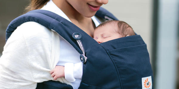 抱っこ紐に抱かれている新生児