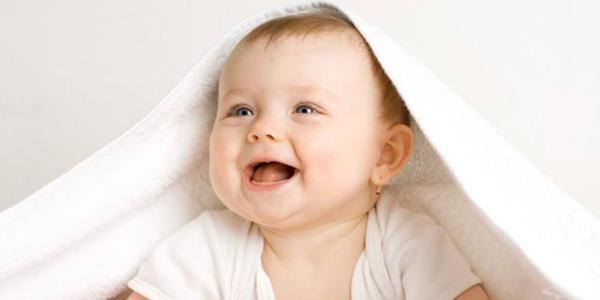 お布団をかぶって笑顔の赤ちゃん